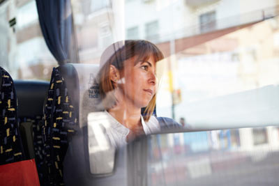 young woman looking out of window on ALSA bus in Spain by Janie Airey photographer