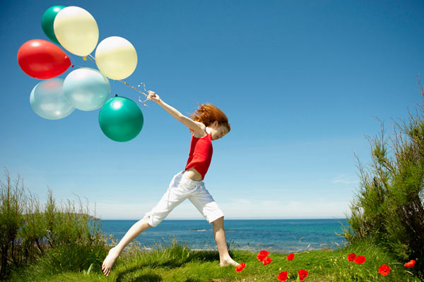 young girl running with colourful balloons against blue sky by Janie Airey photographer