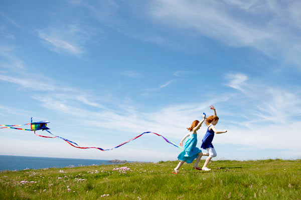 two girls running in field with kites and blue sky by Janie Airey photographer