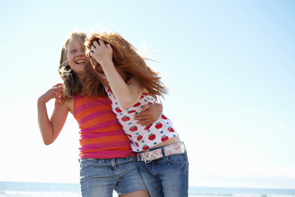 2 girls laughing and hugging on the beach by Janie Airey photographer