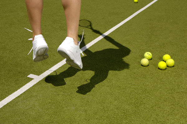 feet of tennis player serving ball by Janie Airey photographer