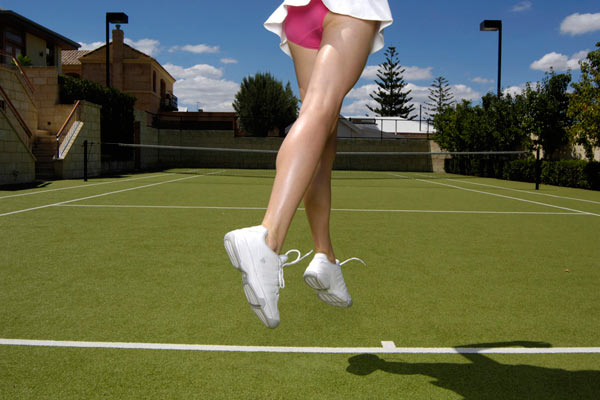 legs of tennis player with pink knickers on court serving ball by Janie Airey photographer