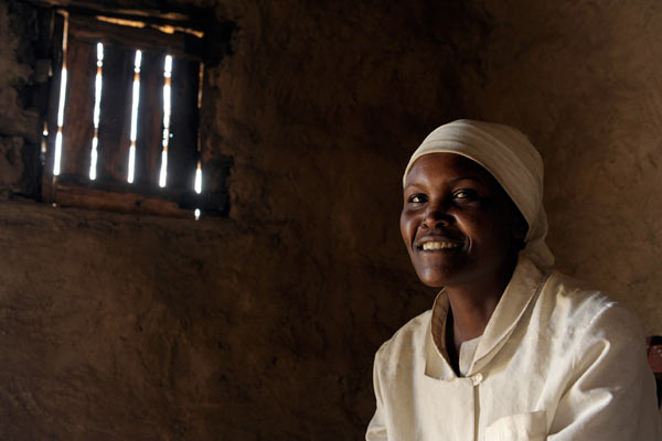 Kenyan nurse in white in mud house by Janie Airey photographer