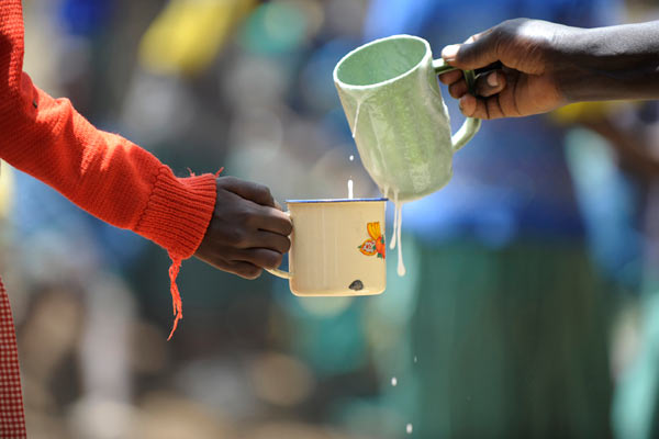 Kenyan child holding tin mug for food aid by Janie Airey photographer