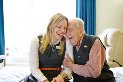 elderly care home resident with care worker laughing at Royal Star & Garter by Janie Airey photographer