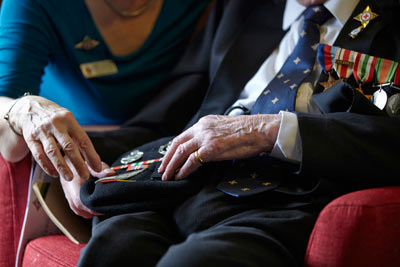Elderly man and carer looking at military medals at RS&G care home by Janie Airey photographer