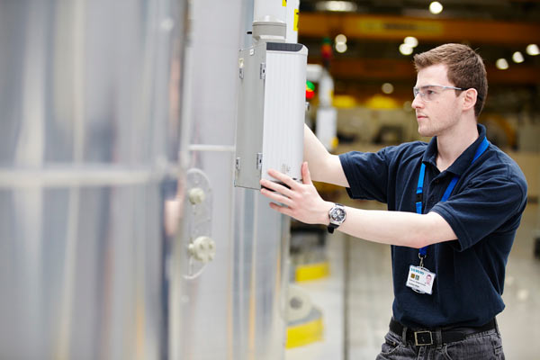 young man at machine in Siemens factory by Janie Airey photographer