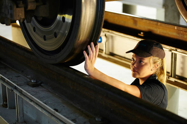 young woman inspecting train wheel in Siemens depot by Janie Airey photographer