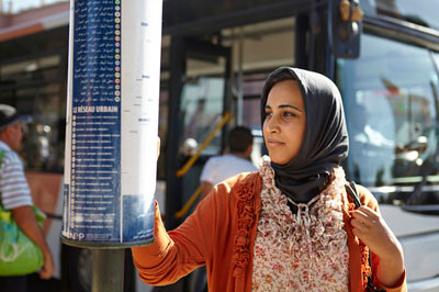 woman in headscarf checking bus timetable in Marrakech by Janie Airey photographer
