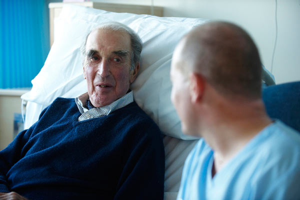 elderly gentleman waiting to be discharged chatting with nurse by Janie Airey photographer