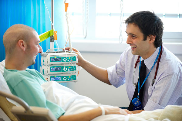 young male doctor chatting with patient in hospital bed by Janie Airey photographer