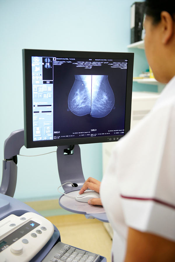 nurse looking at mammogram on computer screen by Janie Airey photographer