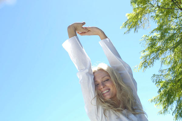 young blonde woman in white stretching in morning sunshine by Janie Airey photographer