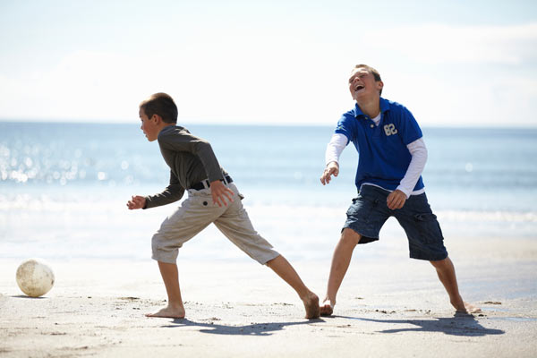 2 boys playing football at the beach by Janie Airey photographer