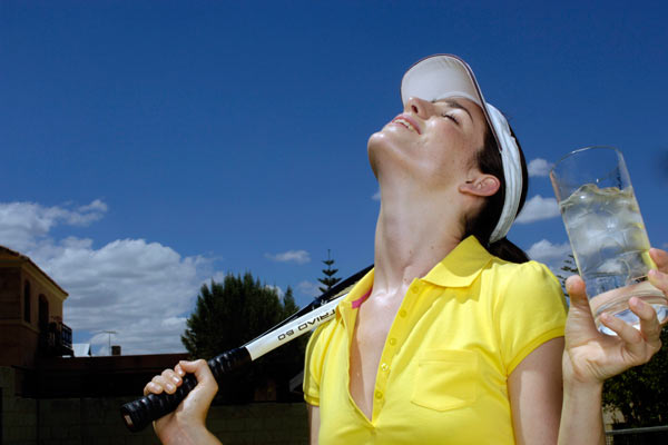 tennis player taking large glass of water in a break from play by Janie Airey photographer