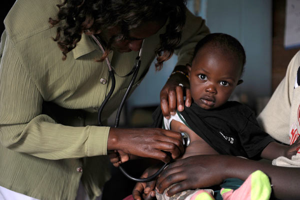 young Kenyan child being checked with stethoscope by nurse by Janie Airey photographer