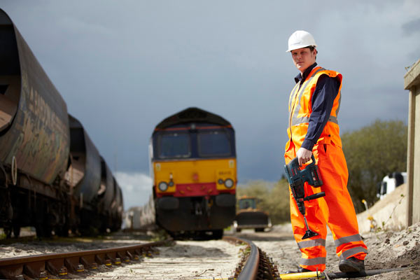 Technical engineer working by railway track with train by Janie Airey photographer