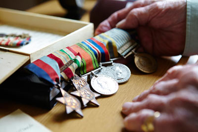Elderly man holding military medals at RS&G care home by Janie Airey photographer