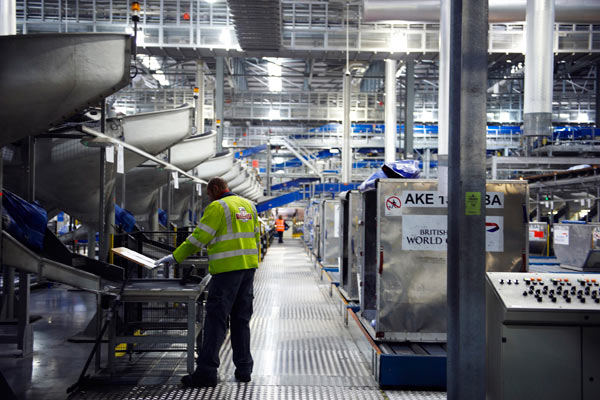 man in high vis vest at large Post office sorting depot by Janie Airey photographer