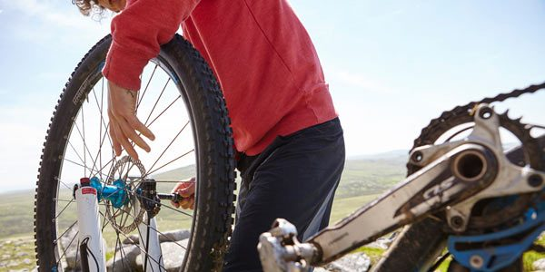 man fixing bicycle on mountain by Janie Airey Potography